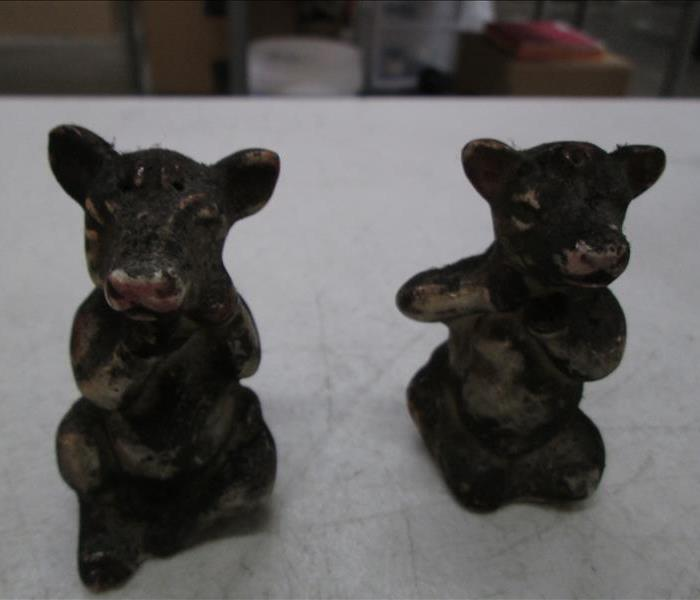Cow salt and pepper shakers covered in soot