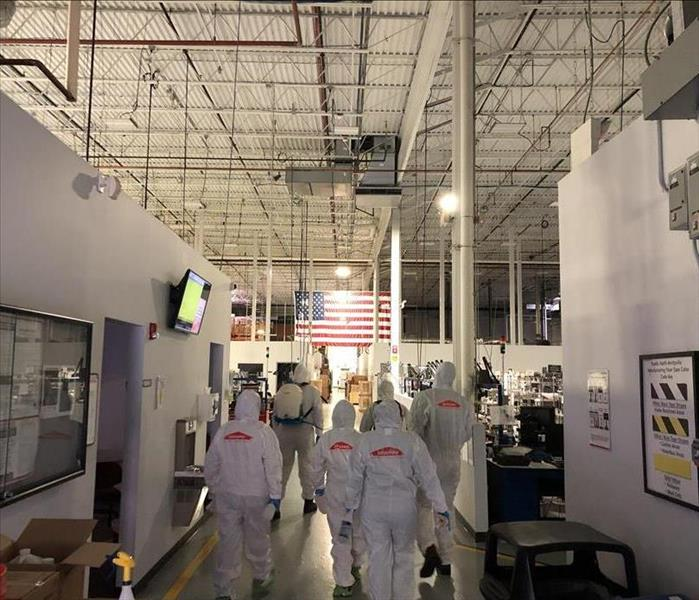 SERVPRO members walking in a business with tyvek suits